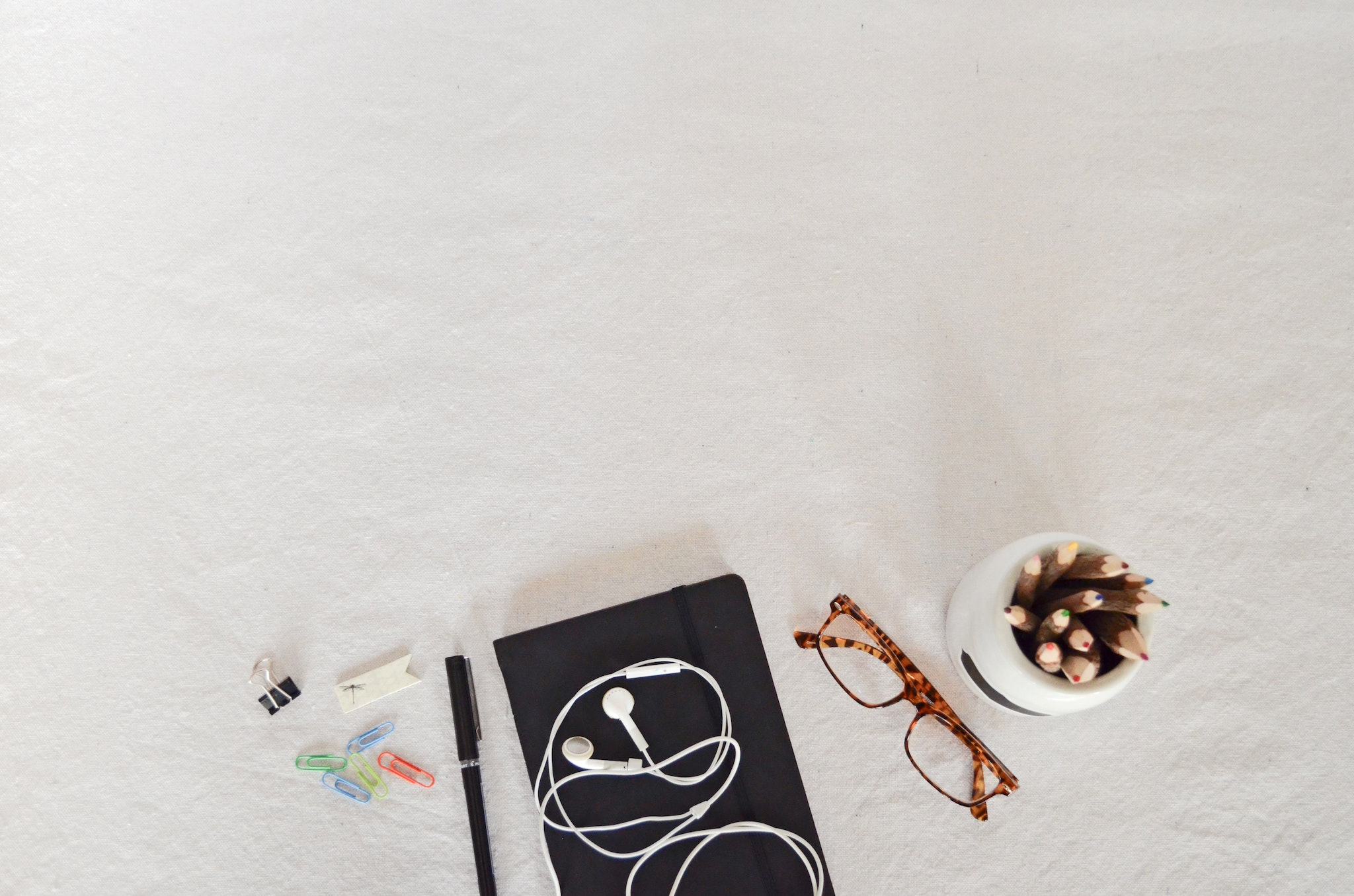 Schools items are laid out on a white surface, including: paperclips, a pen, a notebook with a pair of headphones on top, reading glasses and a cup of colored pencils.