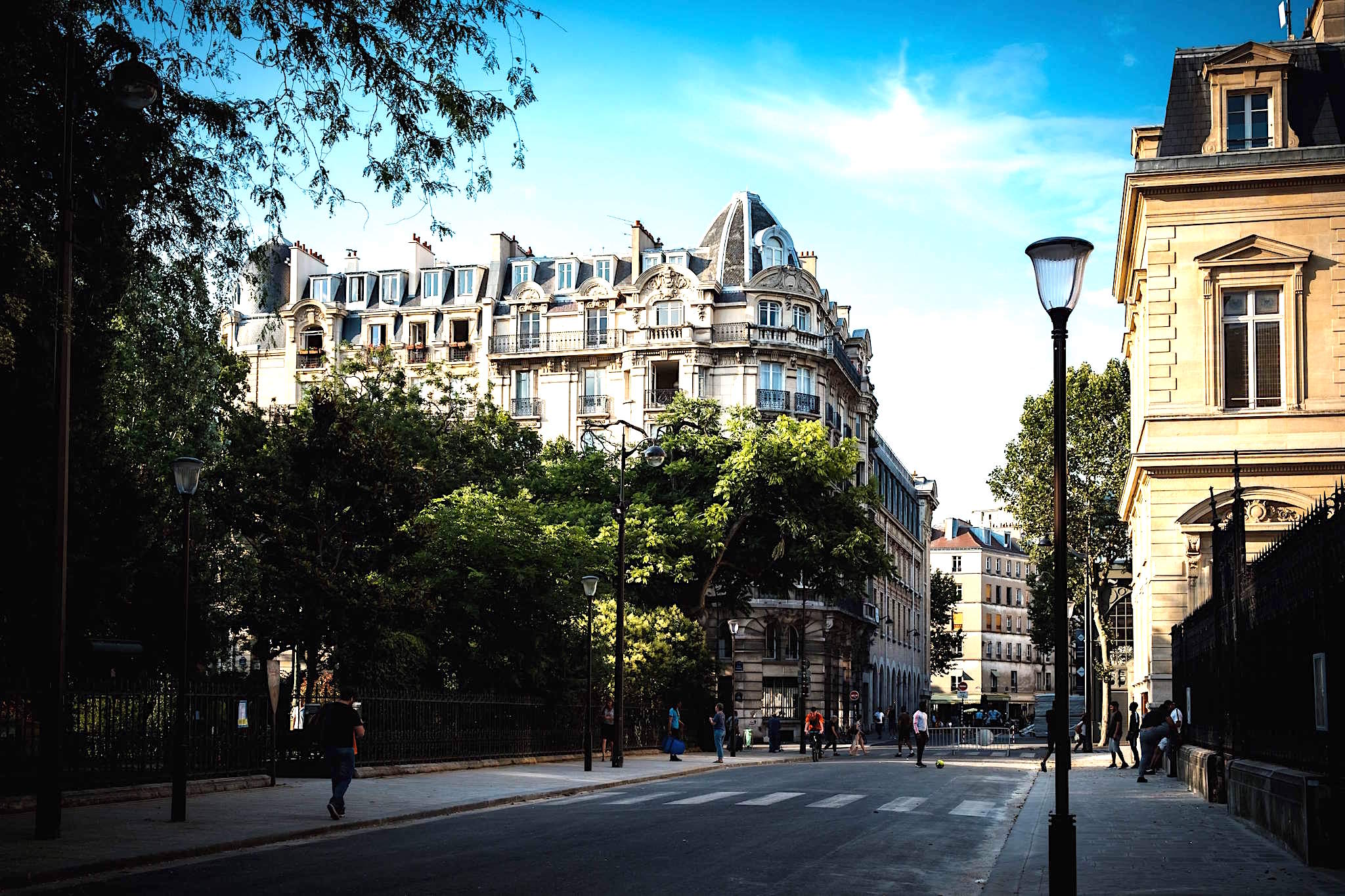 The sun hits the top of a beautiful Haussmann style apartment and green trees as pedestrians walk along the street in Paris.