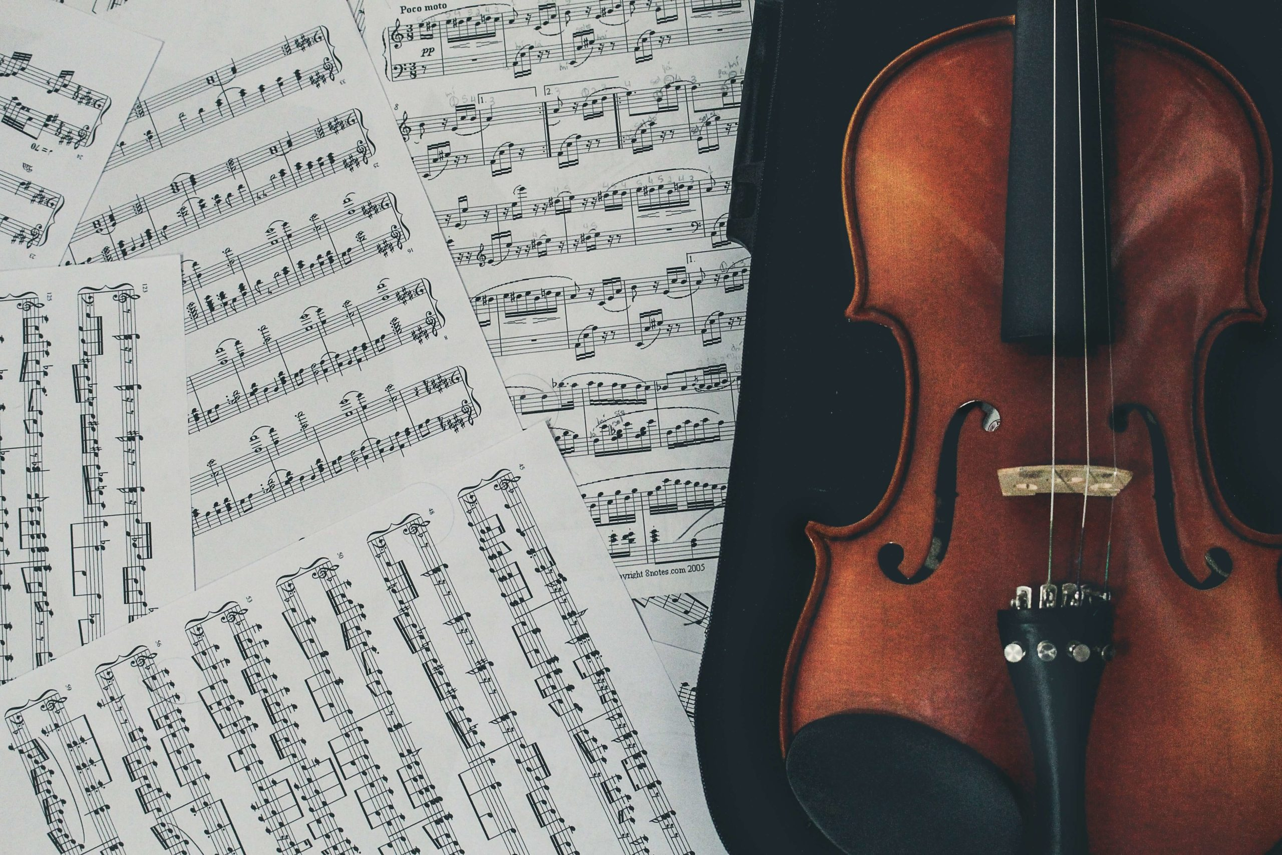 Several sheets of music are laid out on a black surface next to a wooden violin, which has three strings.