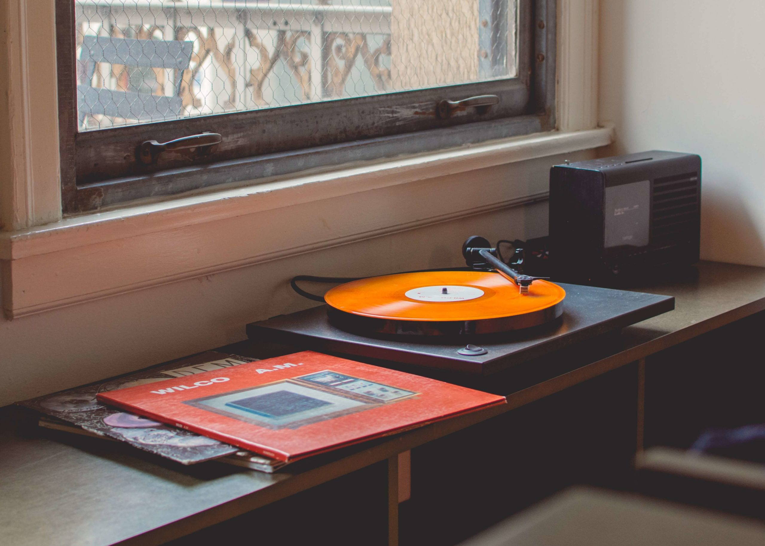 An orange record sleeve lays on a shelf next to a record player, where an orange record is playing music. The  record player sits in the corner of the room in front of a window.