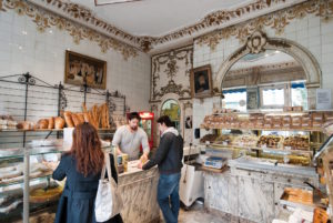 Parisian customers buy baked goods in a beautiful, bright boulangerie