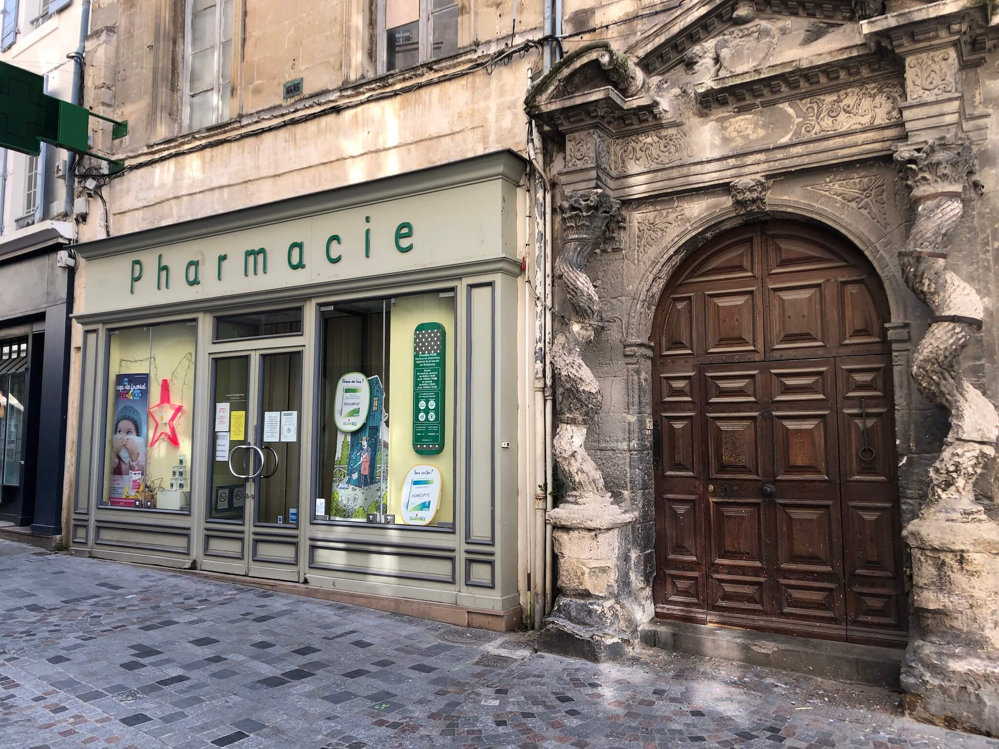 A pharmacie and door to a building on a street in Arles, France.