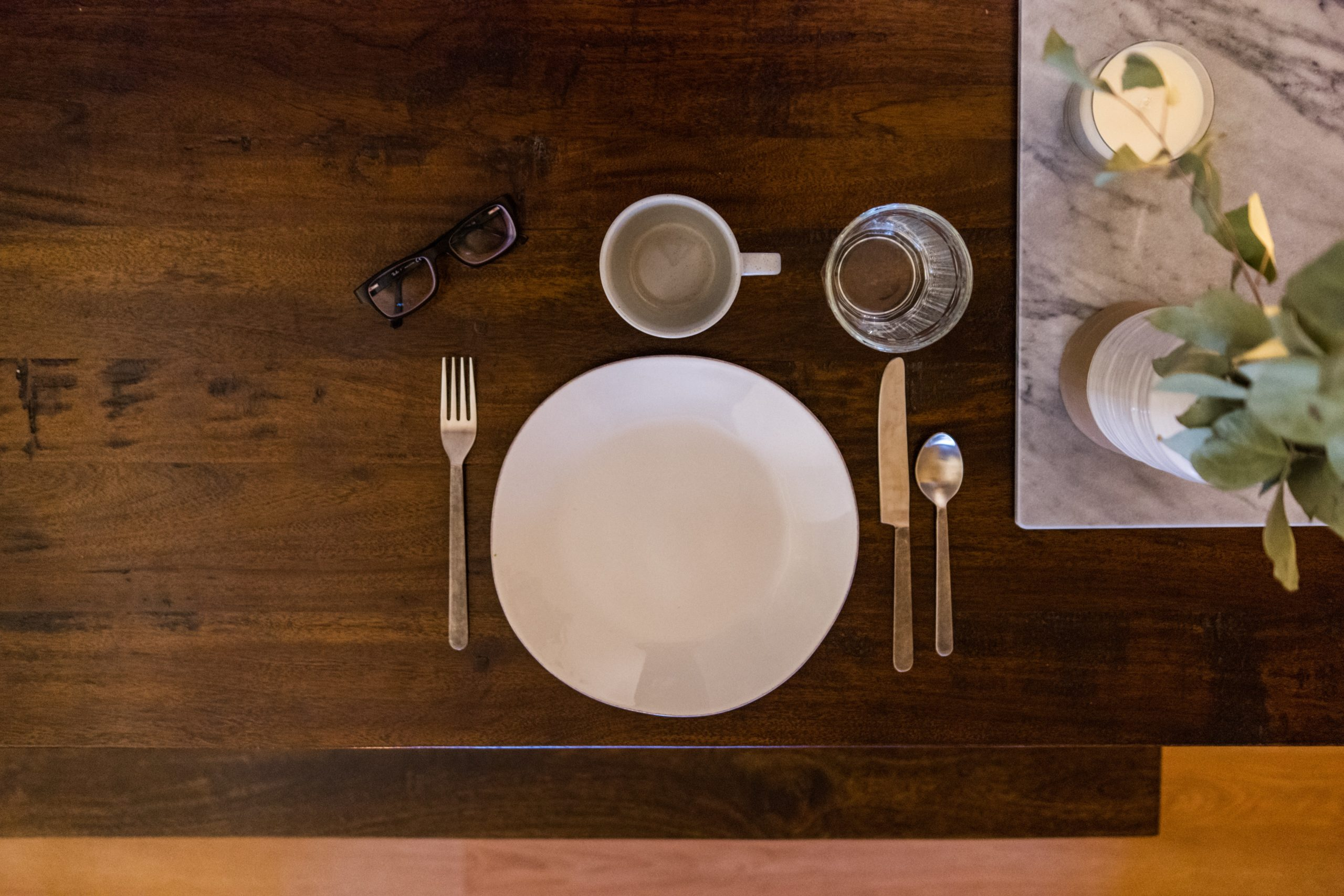 An overview shot of a pair of glasses, a plate, a mug and glass, silverware and a vase of flowers lay atop a wooden table.