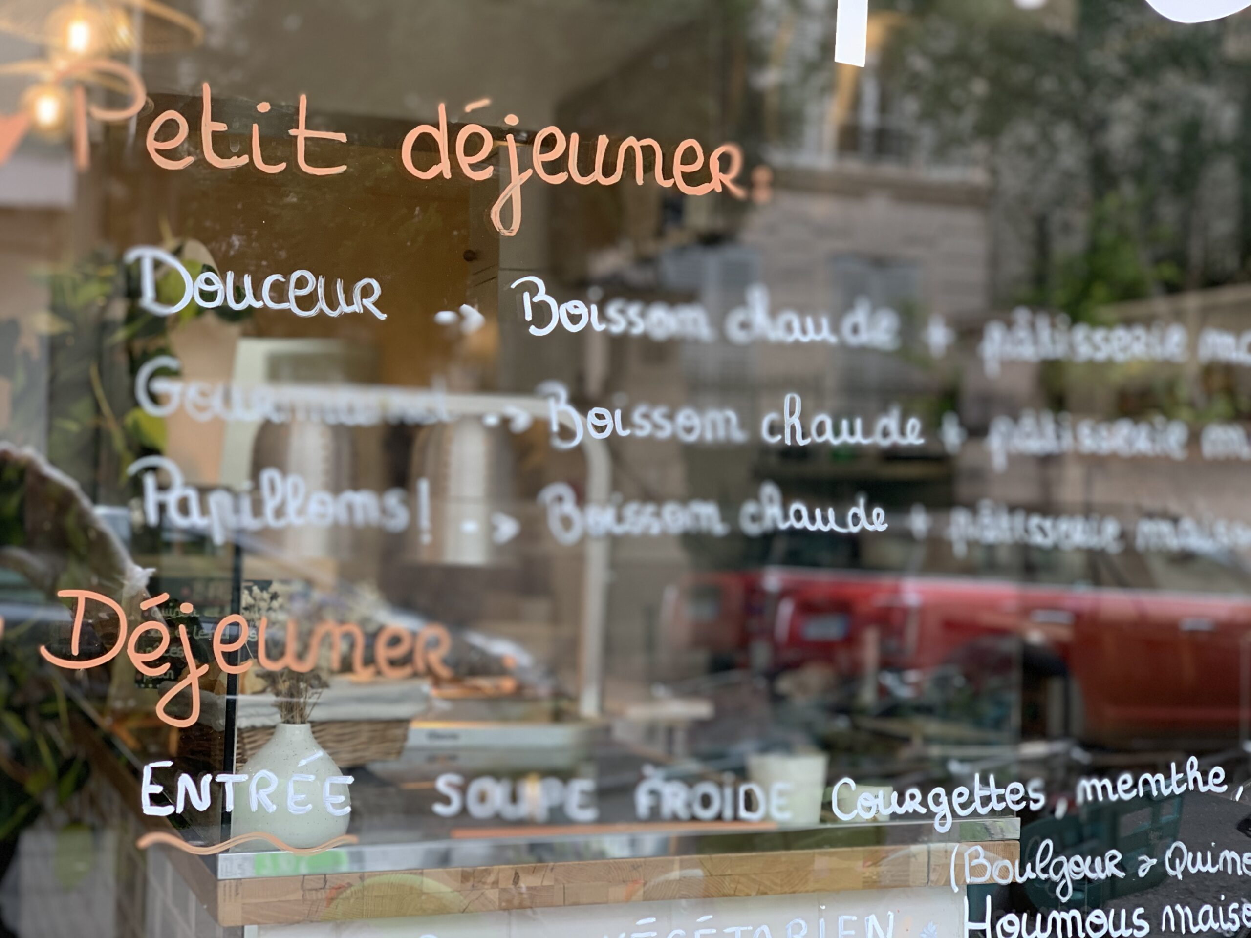 A restaurant menu is written in French on the front glass of a restaurant in Paris.