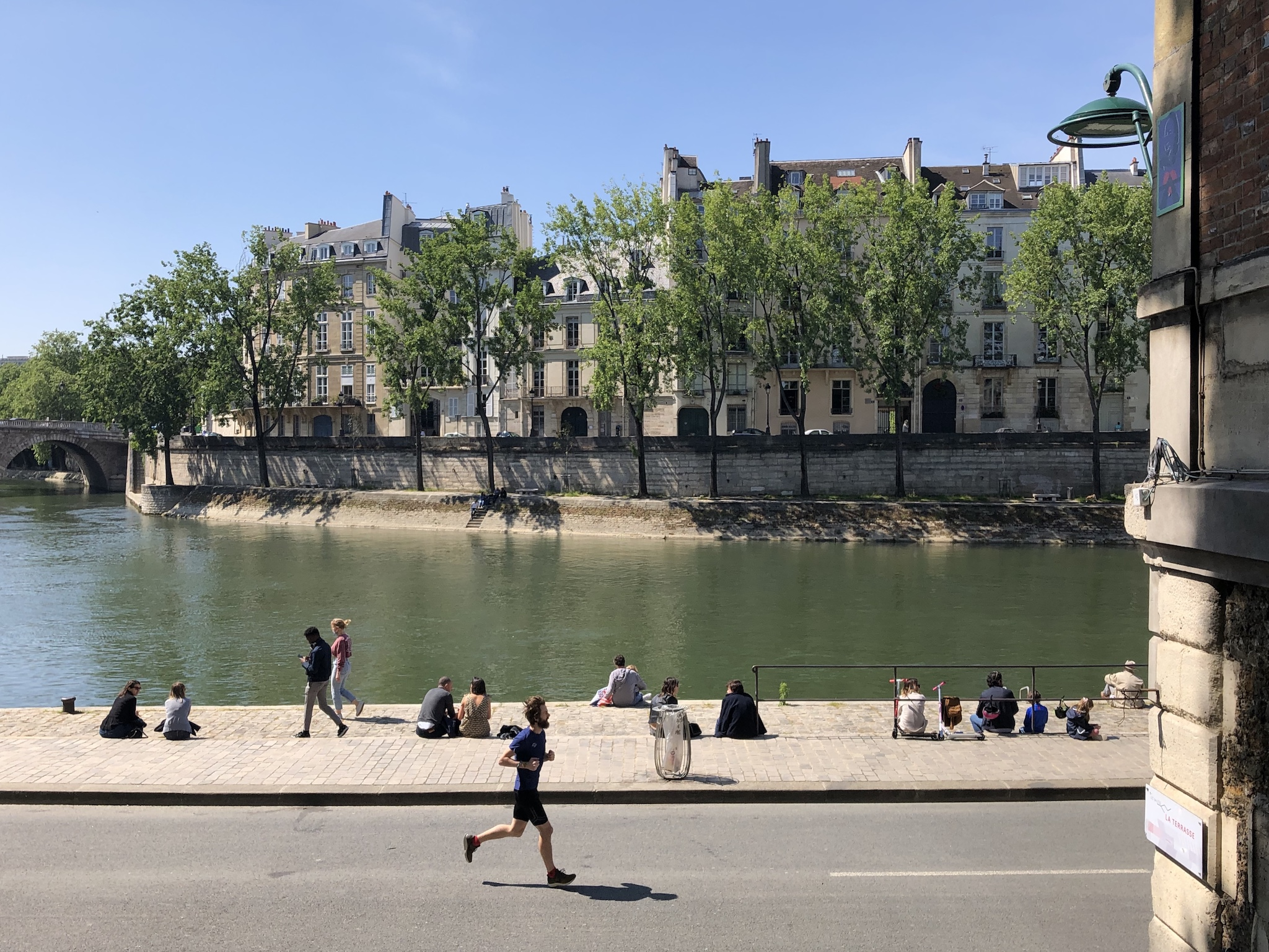 People sit, while distanced, and a man runs along the Seine in Paris on a sunny day after the deconfinement.