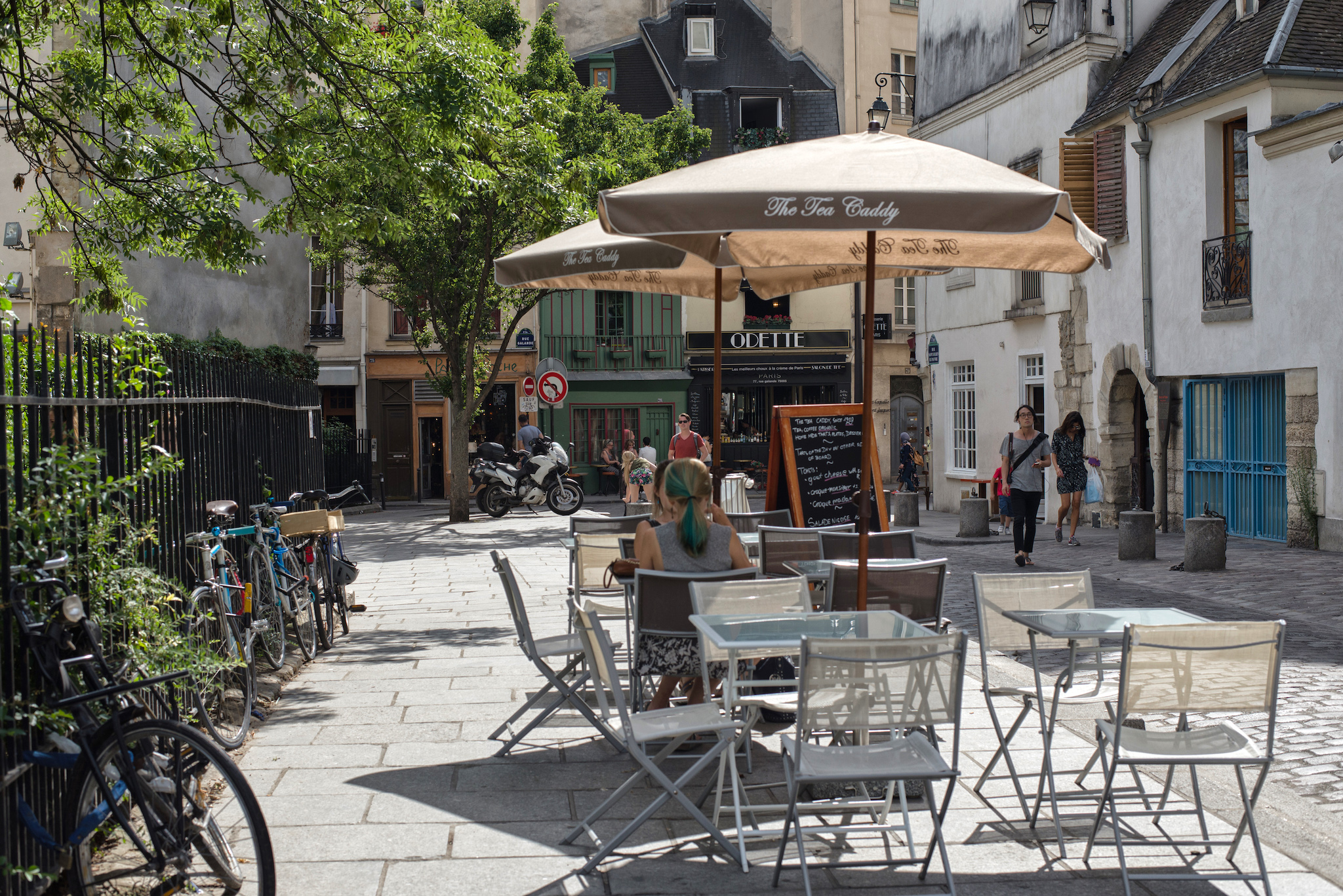 People sit at tables and chairs and stroll down a street in the left bank of Paris on a sunny day.