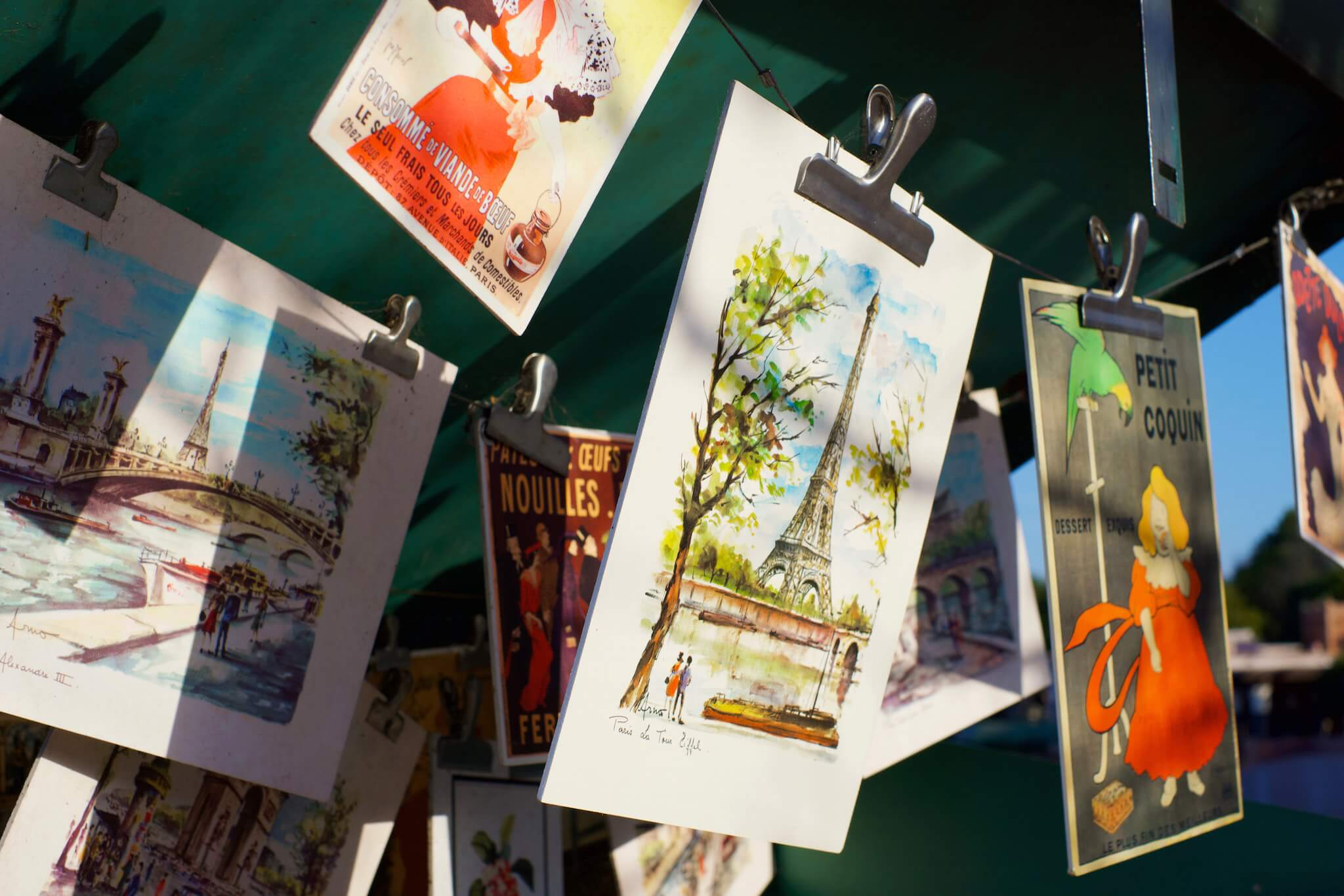 Beautiful hand-painted street art hangs from a vendor's booth along the Seine in Paris.