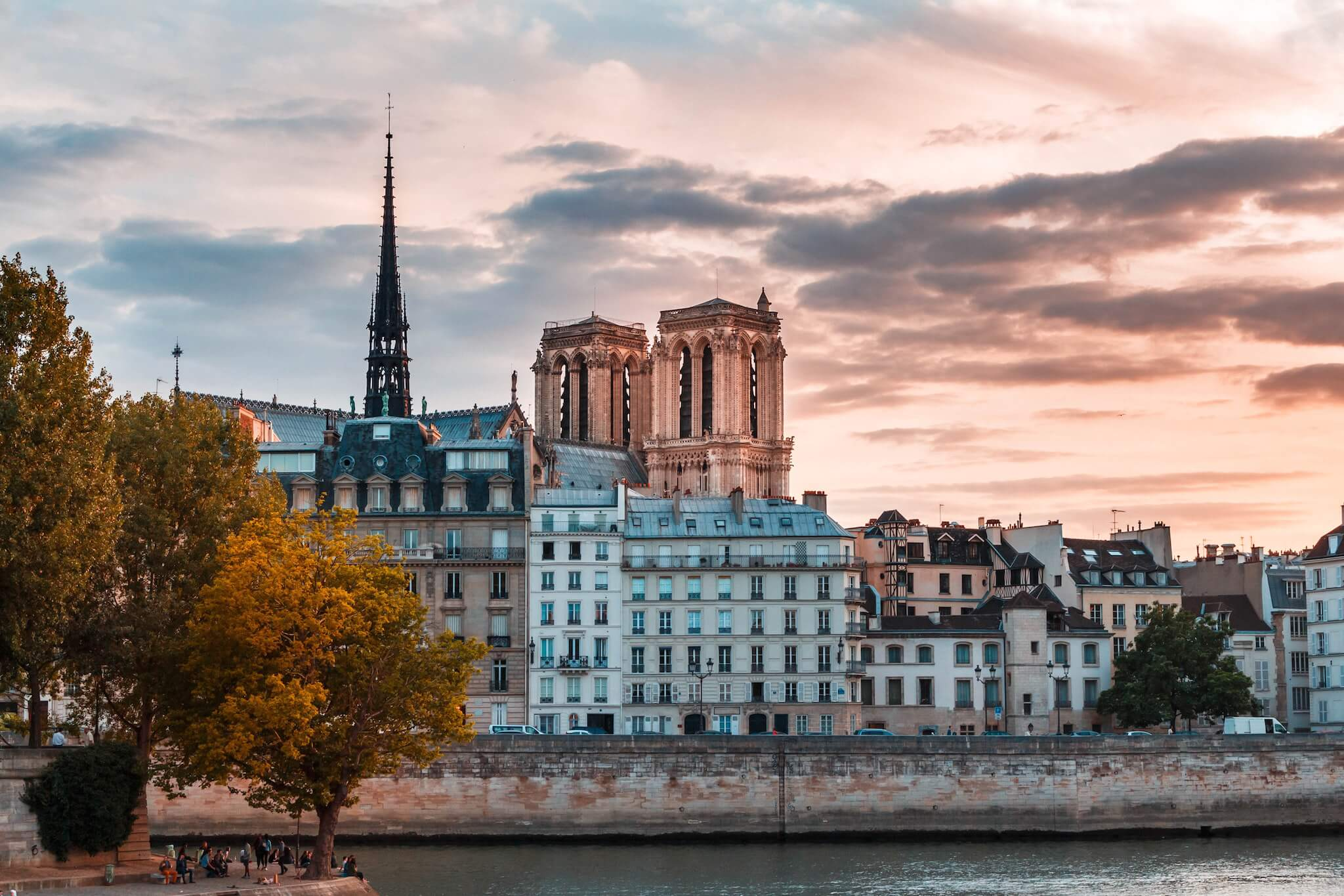 A view of Pont-Neuf, the Seine, Parisian apartments, and in the background, Notre-Dame, at sunset.