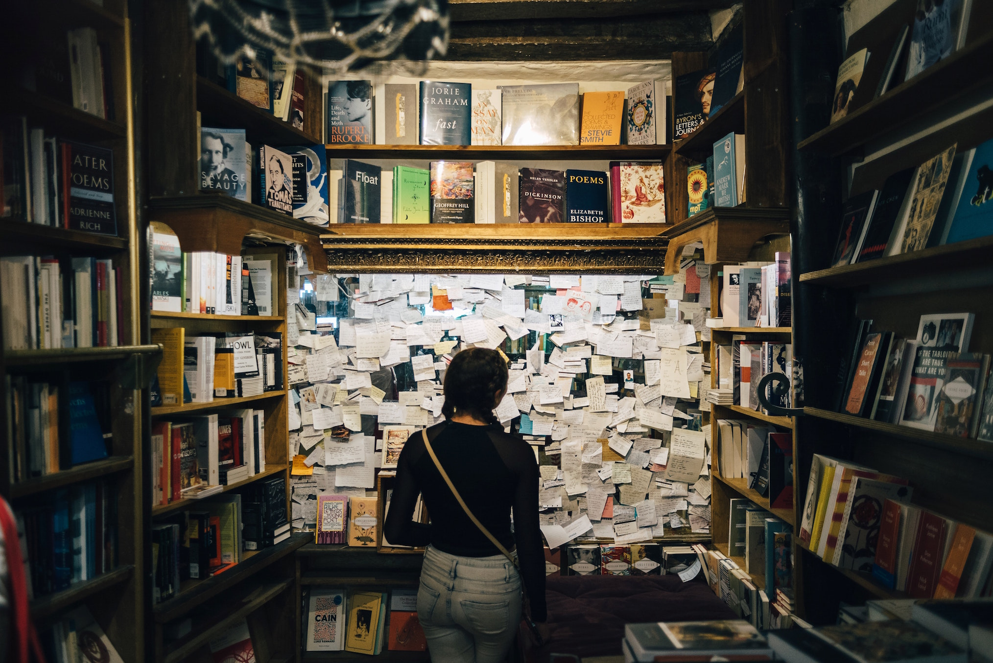 A woman stands in a section of Shakespeare & Company bookstore in Paris, reading notes past customers have left behind