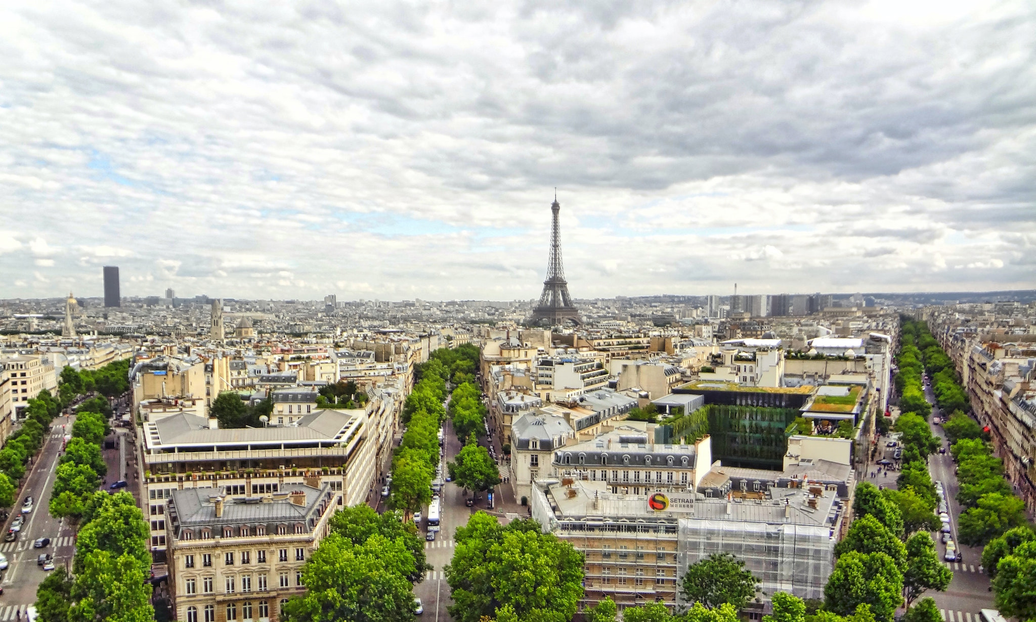 A view of Parisian rooftops, tree-lined streets and the Eiffel tower is visible from a high view.