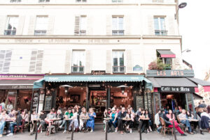 "People sit on terraces of restaurants in Paris' Latin Quarter. The names of the restaurants include, ""Bistro Italien, ""Gaston,"" and ""Café des Arts"""
