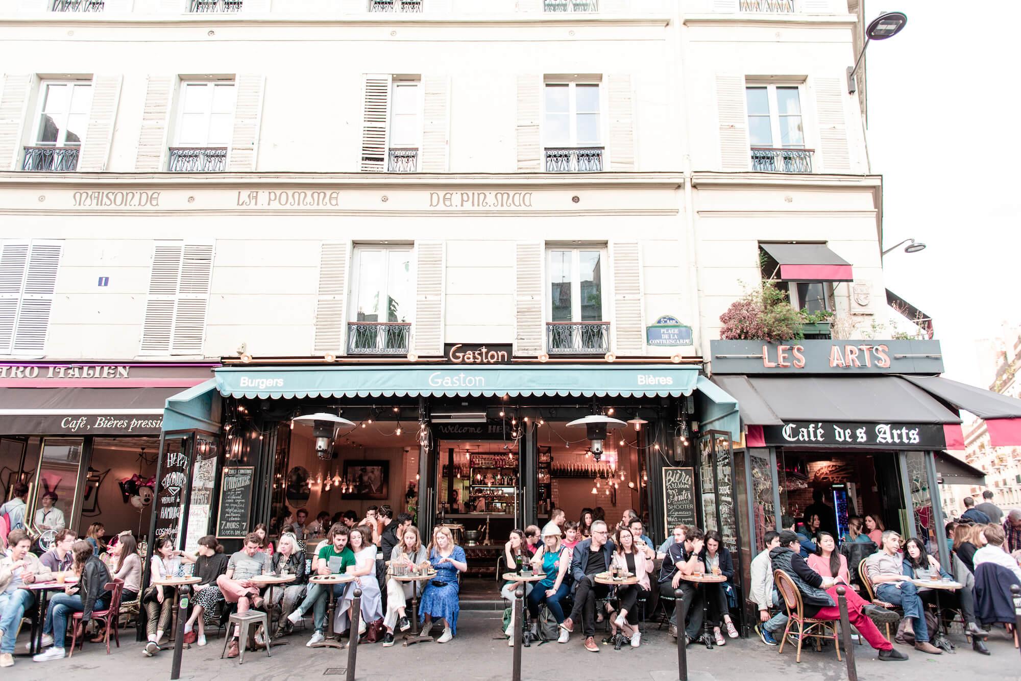 "People sit on terraces of restaurants in Paris' Latin Quarter. The names of the restaurants include, ""Bistro Italien, ""Gaston,"" and ""Café des Arts"""