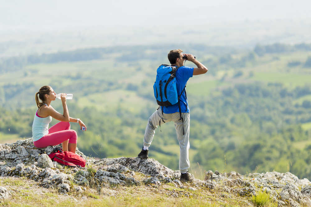 Image of a young couple being active while hiking and mountain climbing.