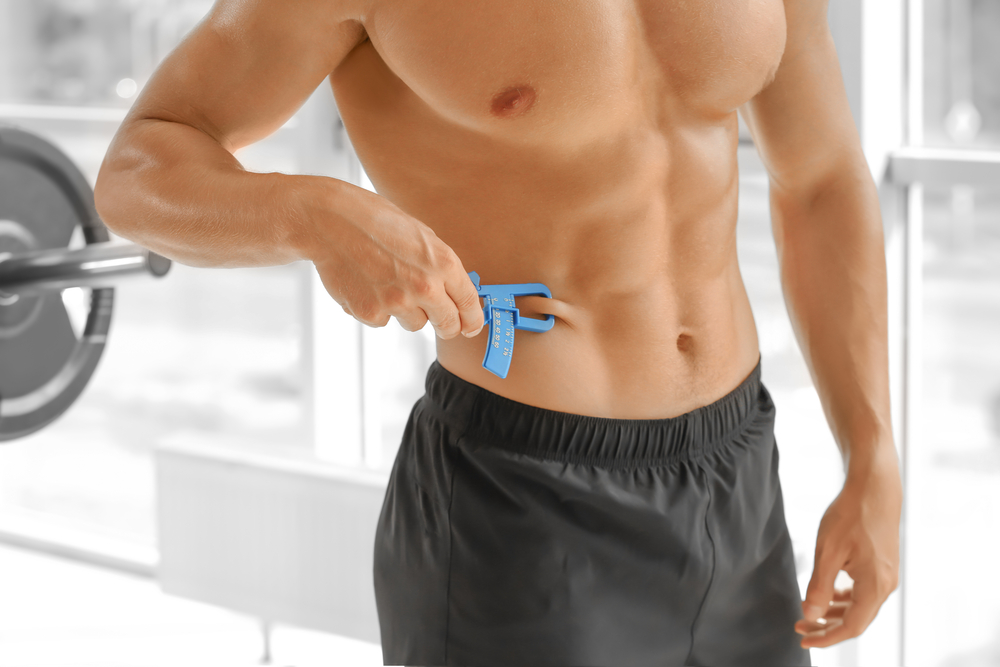 Image of a man measuring his body fat percentage using a skin fold caliper or skin fold calipers.