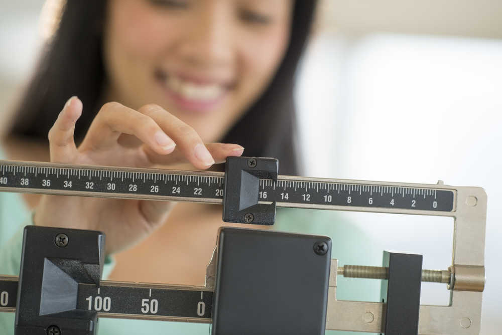Image of a woman weighing herself on a scale in kg or kilograms.