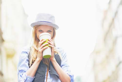Image of a young woman drinking coffee similar to Starbucks from a paper coffee cup.