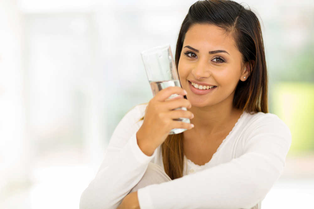 Image of a young woman drinking water.