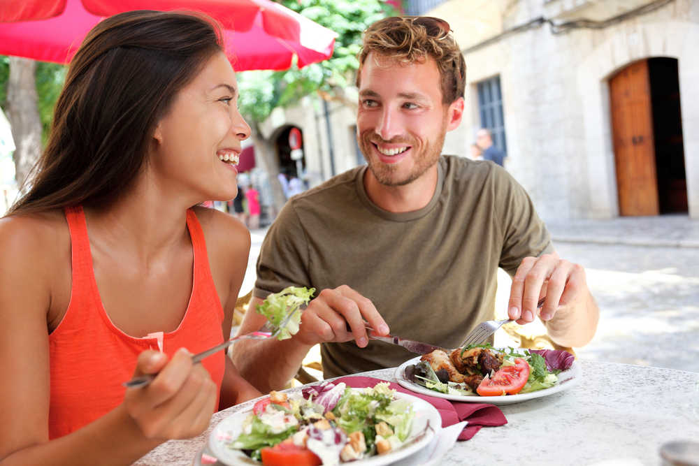 Image of a woman and man eating salad and lean protein making a healthy food choice with low calories.