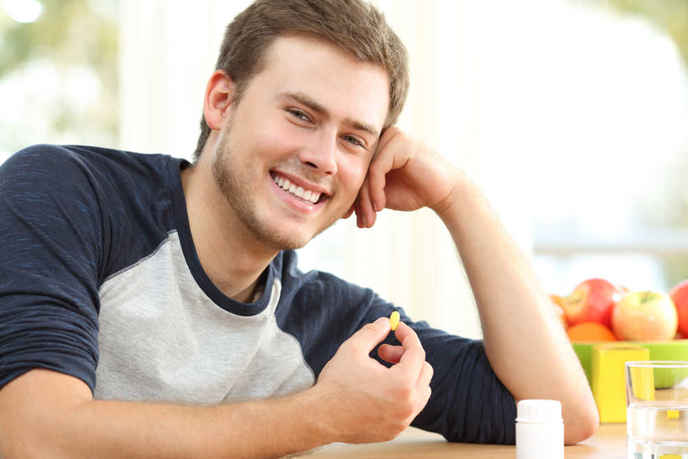 Image of a young man taking supplements such as vitamins, minerals, and amino acids.