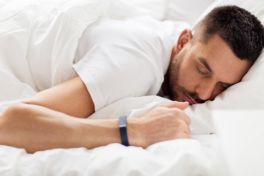 Image of a man sleeping while wearing a fitness tracker or sleep tracking device.
