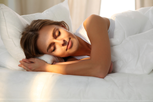 Image of a woman sleeping peacefully in a comfortable bed.