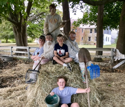 Six boys sit on and around a pile of straw they have cleaned out of the pig stall