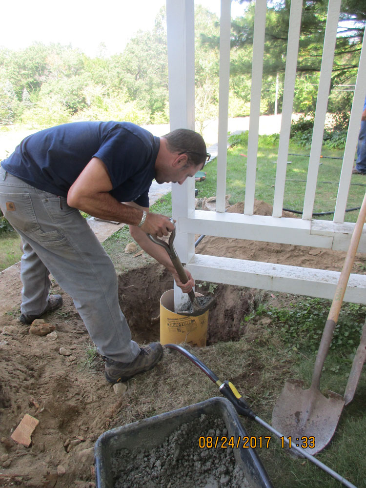 Historic New England carpenter Dave Maloney installing a new footing for the west trellis
