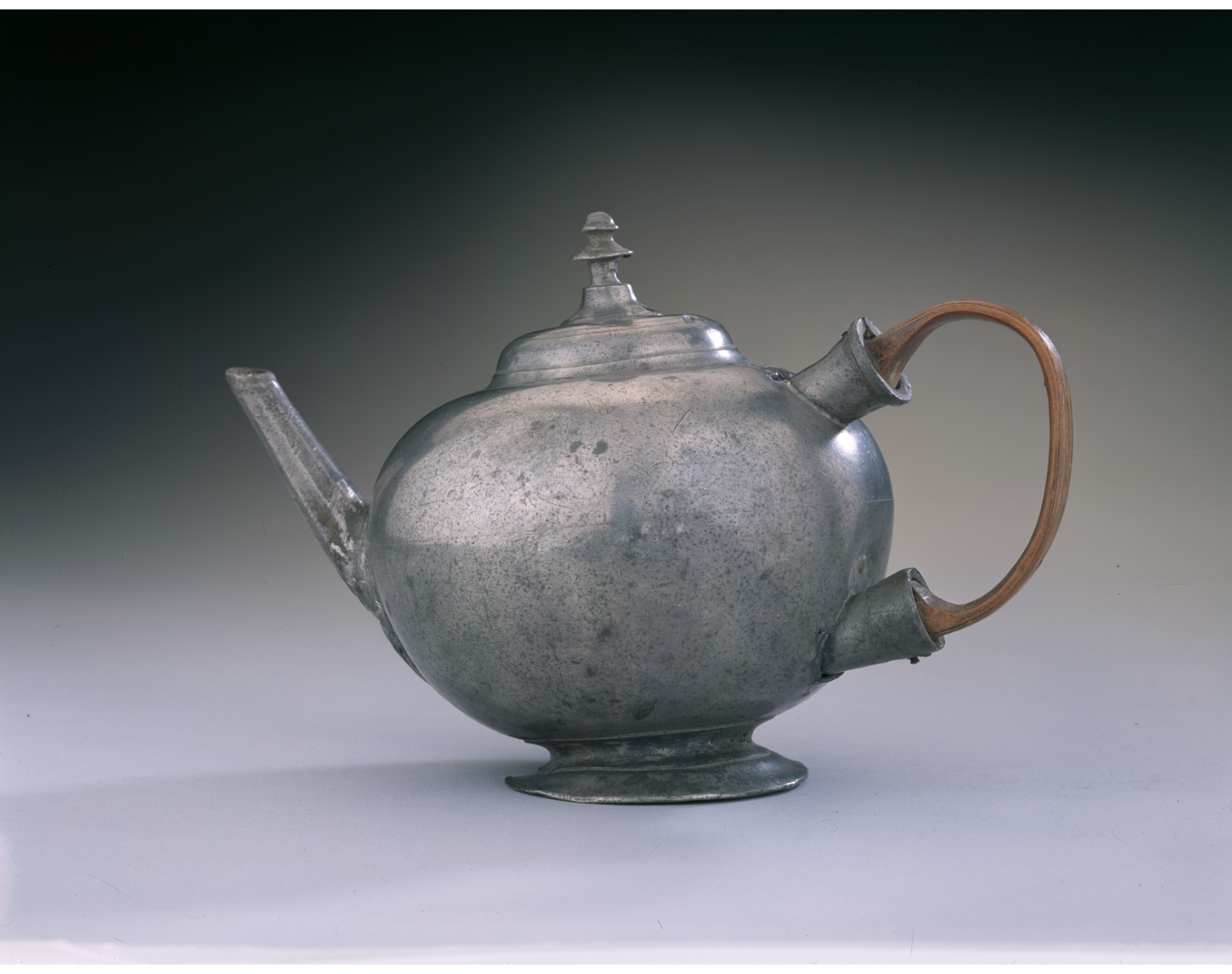 Small round, ball-shaped teapot with domed, hinged lid with ornament on top; globular makeshift wooden handle, straight spout.