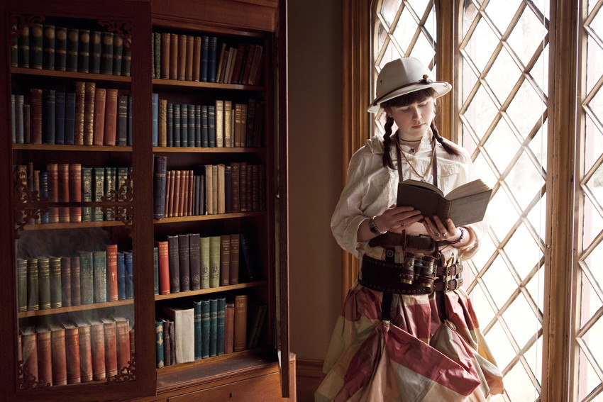 A woman in steampunk-style attire reads a book in the parlor at Roseland Cottage
