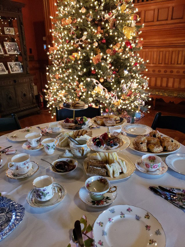 Teacups, tea sandwiches, and pastries are set up in front of a decorated Christmas tree in the great hall of the Eustis Estate