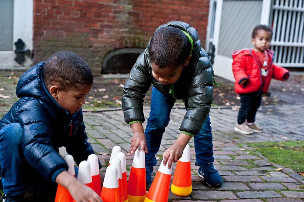 Children play with candy corn-shaped bowling pins during a Wicked Wednesdays program at Phillips House