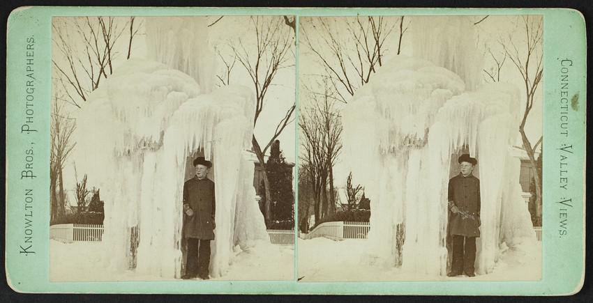 A boy stands under a frozen fountain