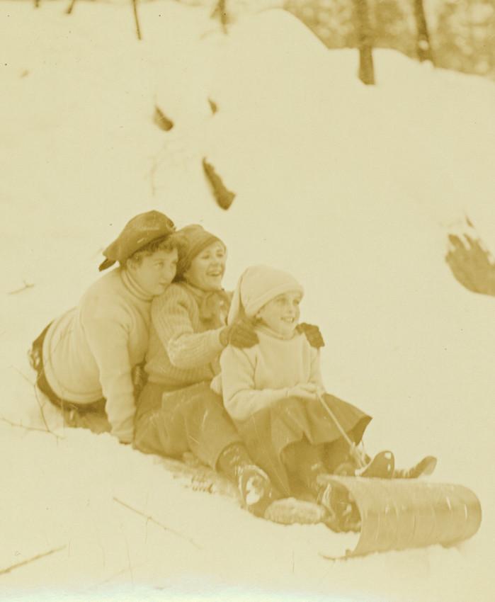 Three girls ride a toboggan