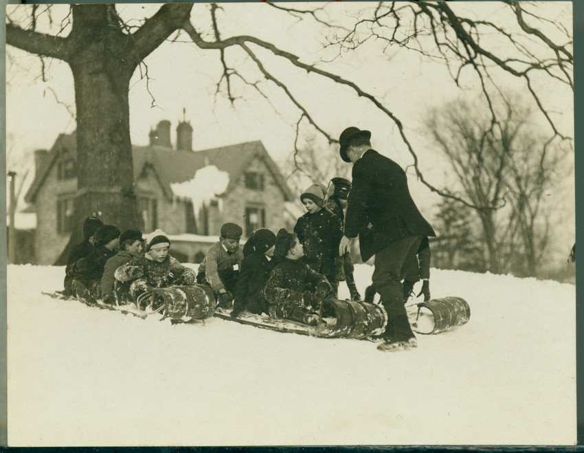 Several children are on a toboggan about to go down a slope