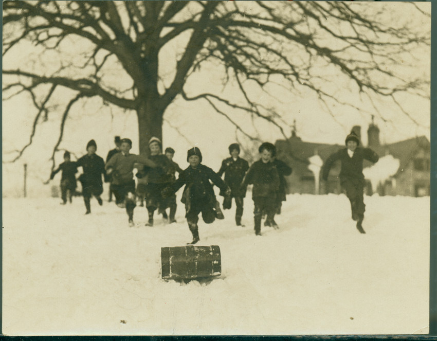 Children run after a toboggan sliding down a slope