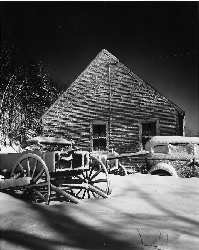 A buggy and a car sit under a blanket of snow next to a house