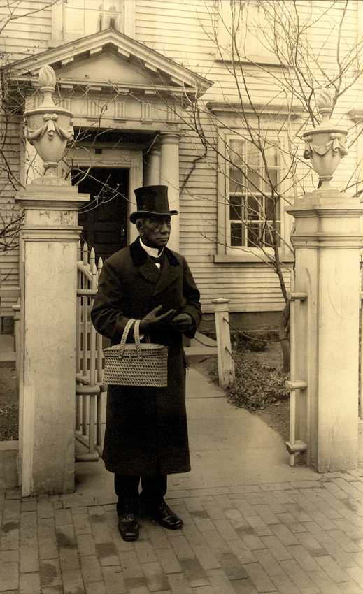 Man (Edward Cassell) stands in front of Nichols House, Salem, Mass. holding a basket. c. 1907