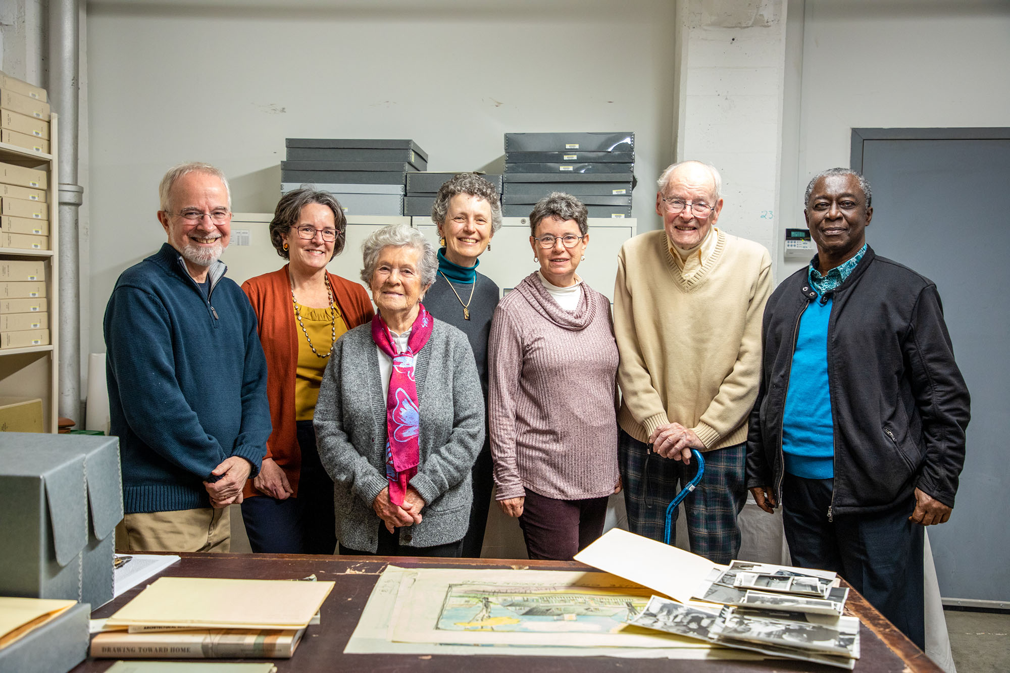 Seven of Royal Barry Wills's family members visiting the Library & Archives pose in front of a table with the architect's sketches.