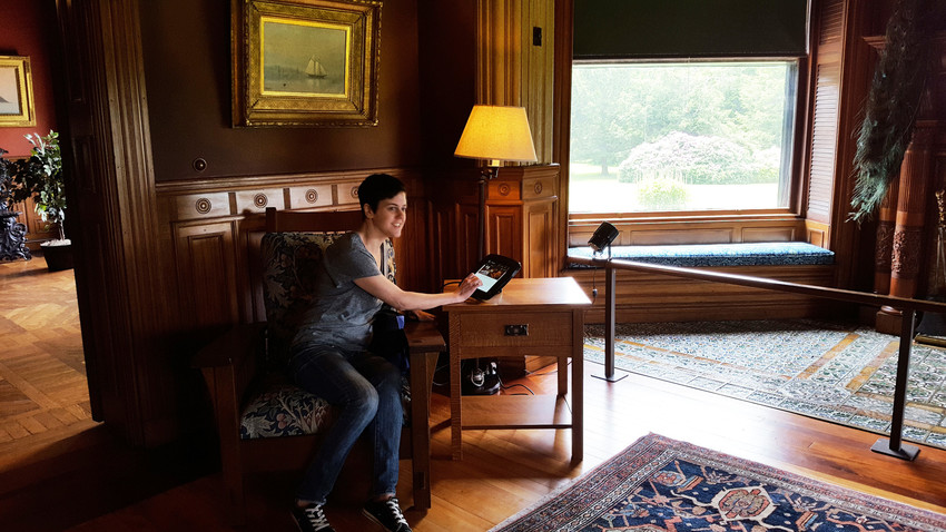 A visitor uses the Eustis Estate tour app while sitting in the large parlor
