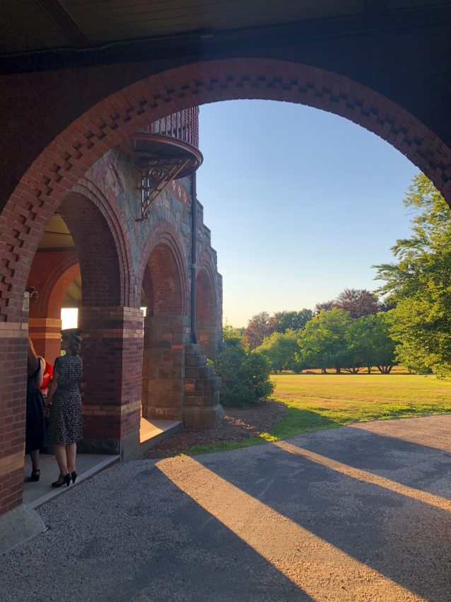 People stand under an archway at the Eustis Estate during sunset.
