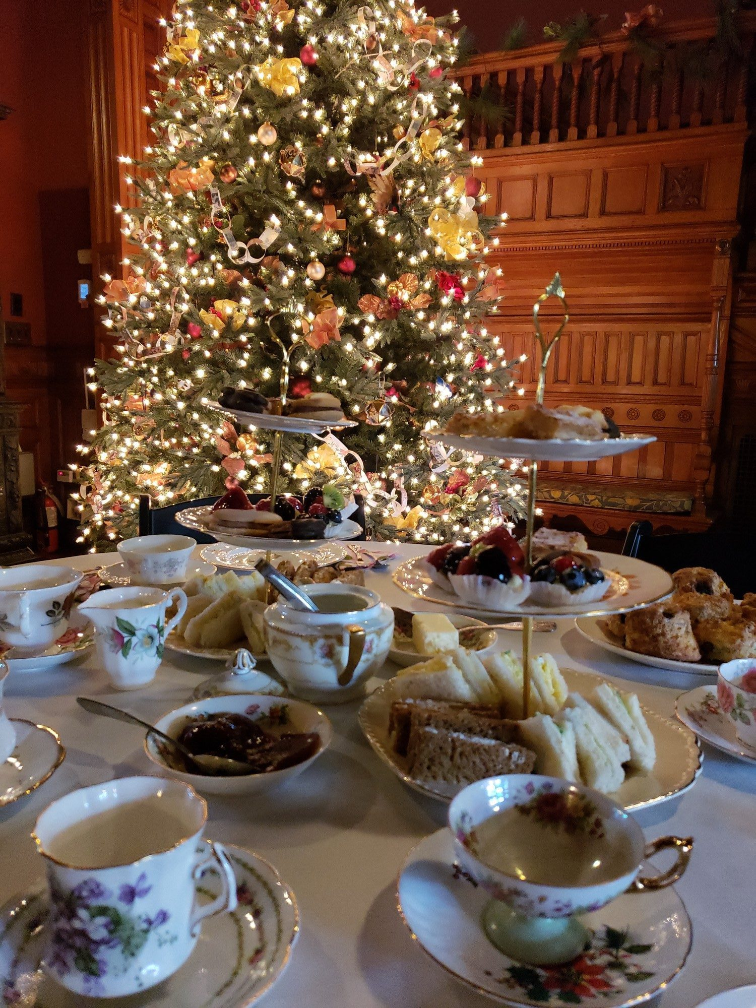 A table with teacups, finger sandwiches, and desserts with a Christmas tree in the background.