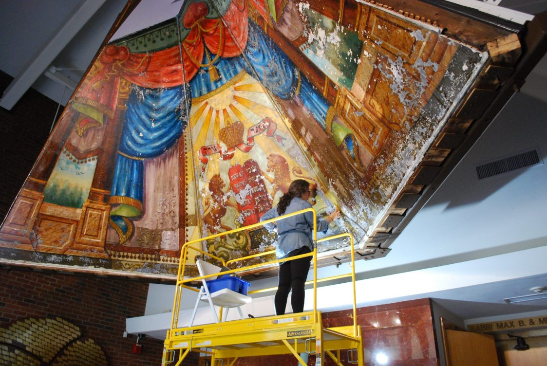 Conservator Emily Phillips carrying out preliminary cleaning of the Lost Mural, in Ohavi Zedek Synagogue in August of 2020.