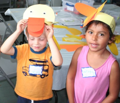 Two small children wearing paper duck masks they have made.