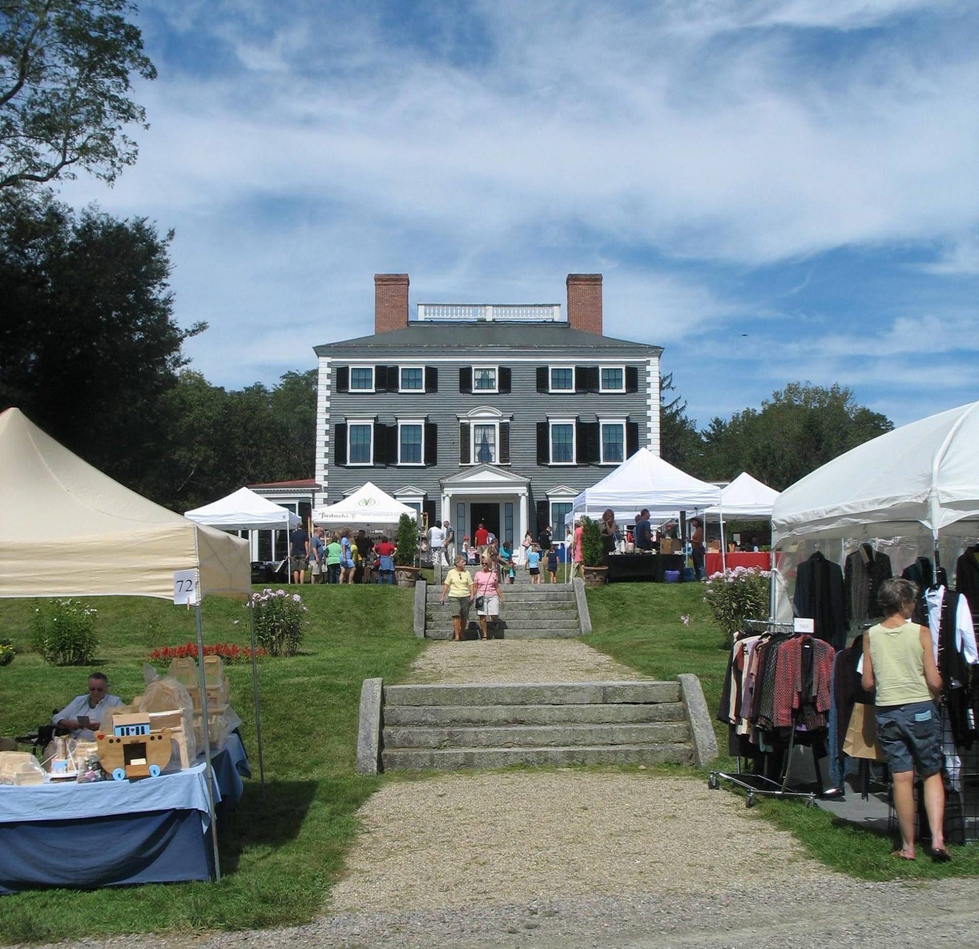 Vendor tents and people shopping on the lawn of the Codman Estate