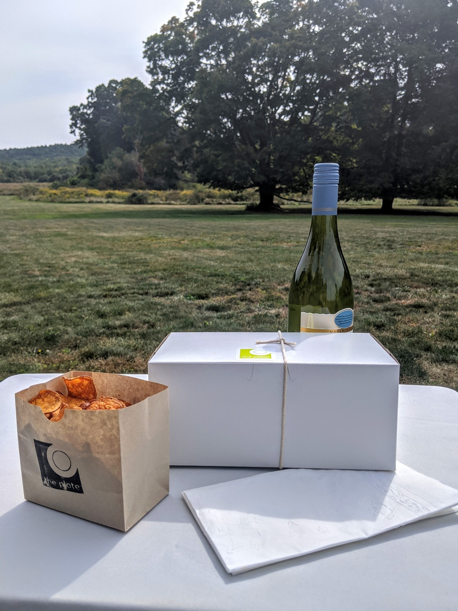 Bottle of wine and catered meal box on a table on the Eustis Estate lawn