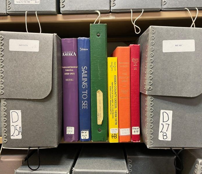 Rainbow colored books on a shelf of archival files