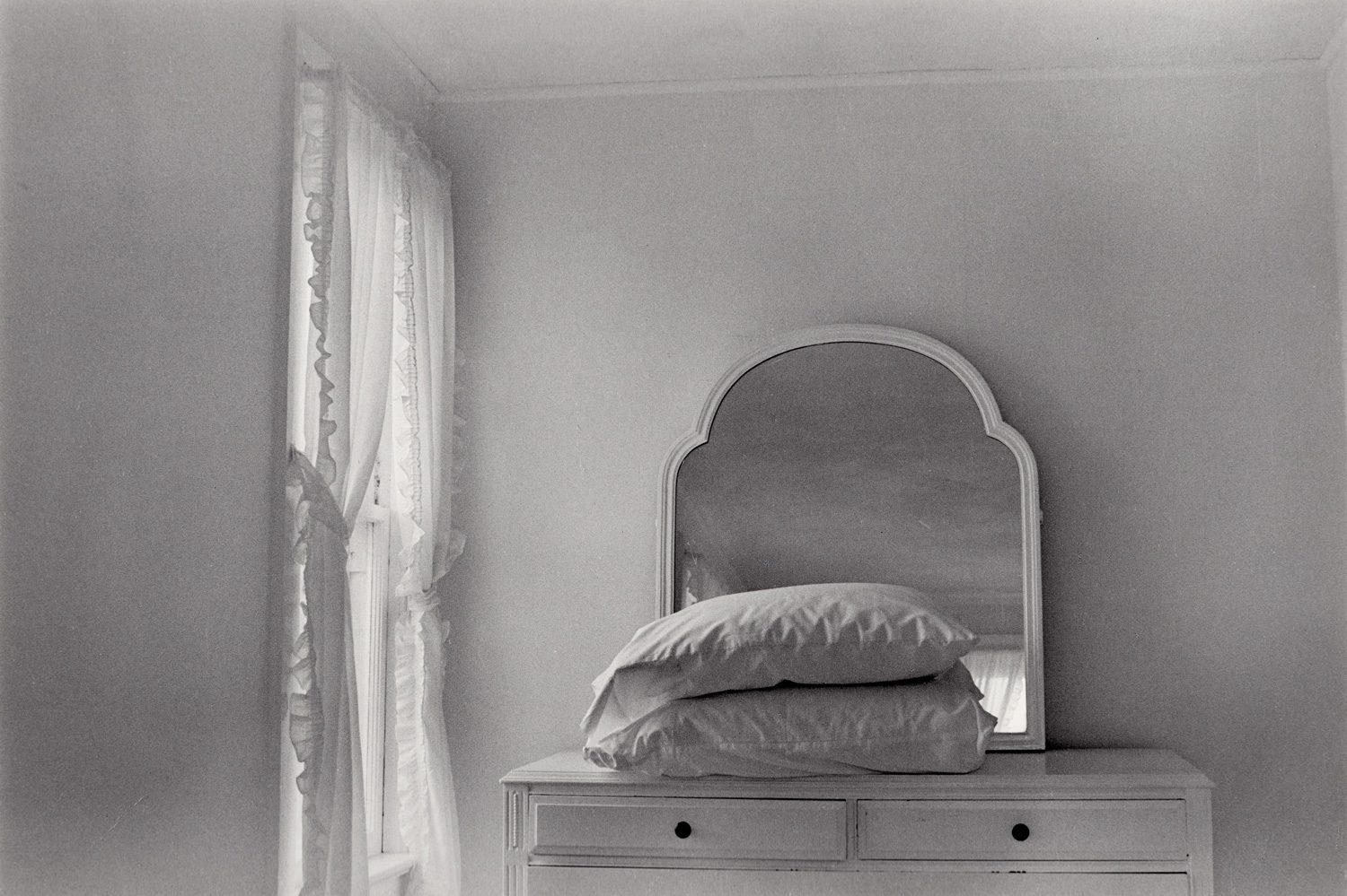 Dresser with Pillows in front of Mirror