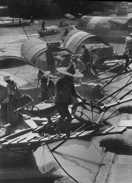 Coolie Carrying Grain Basket at Dock
