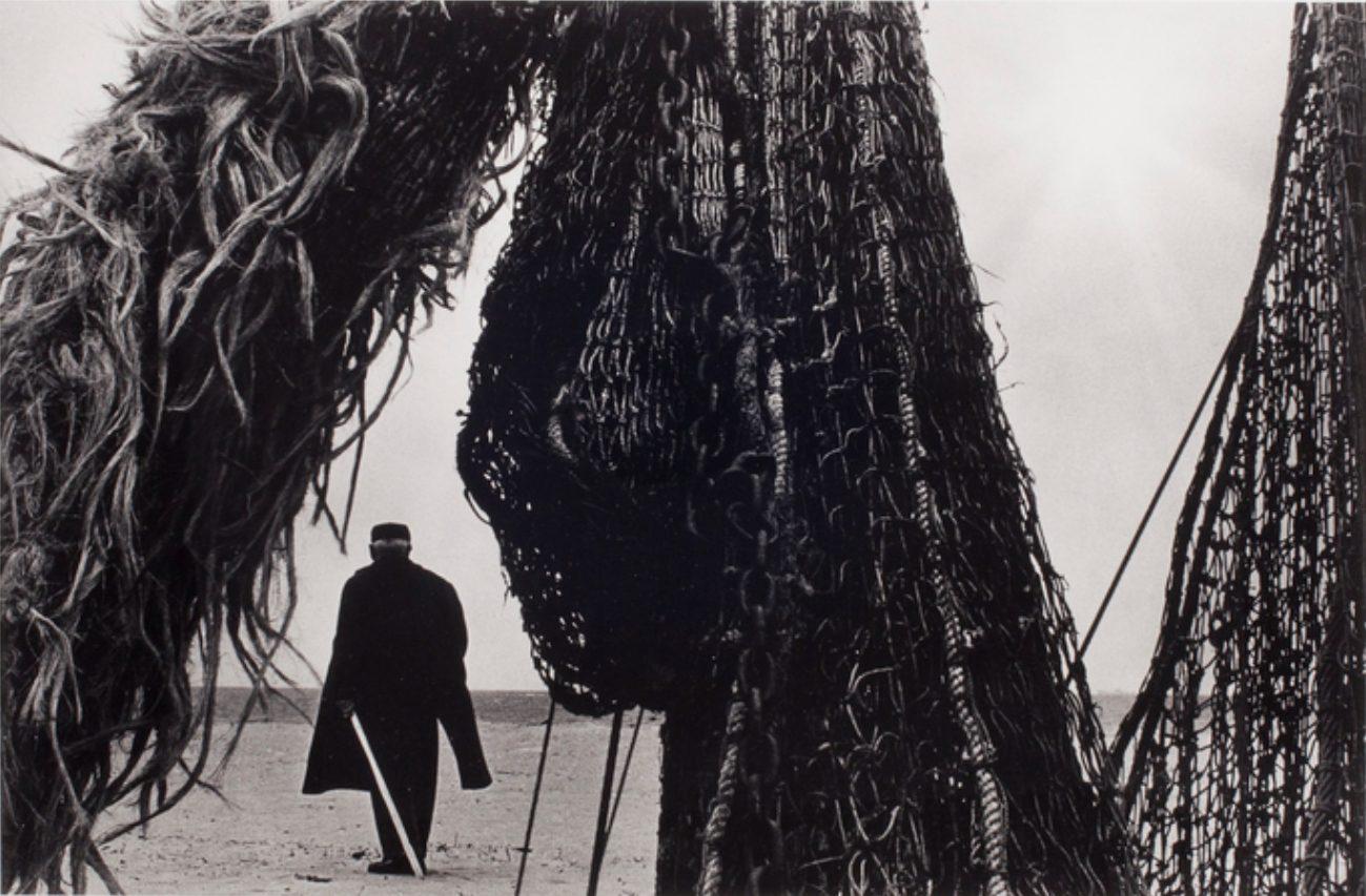 Man on Sand Through Fishing Net