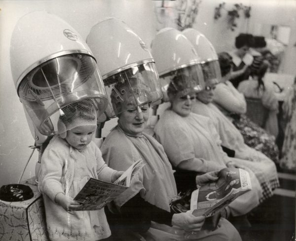Keystone Press Agency, Baby Heather Gets her First Perm - A small girl stands on a chair under a hair dryer